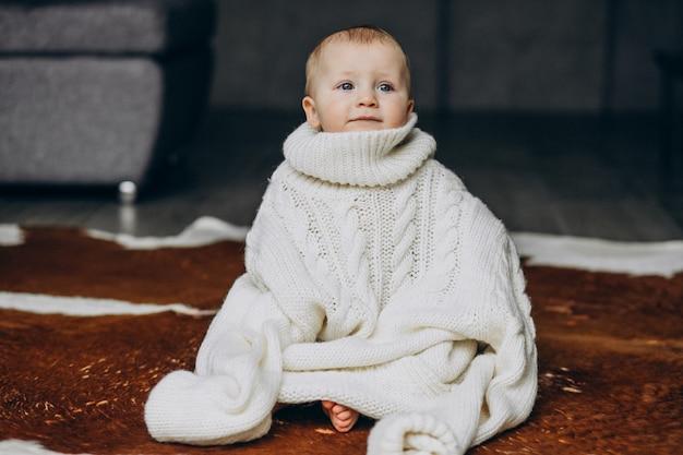 Mały ładny chłopczyk siedzi na podłodze w ciepły sweter