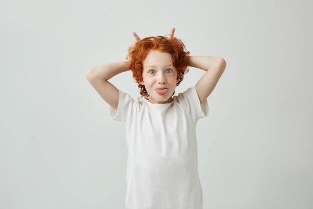 Mały ładny rudy chłopiec w białej koszulce dobrze się bawi, robiąc głupie miny, pokazując język i robiąc rogi palcami.