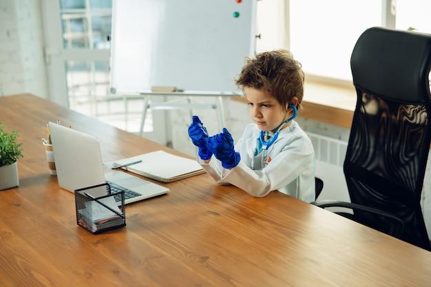 Mały lekarz podczas zabawnego noszenia rękawic ochronnych