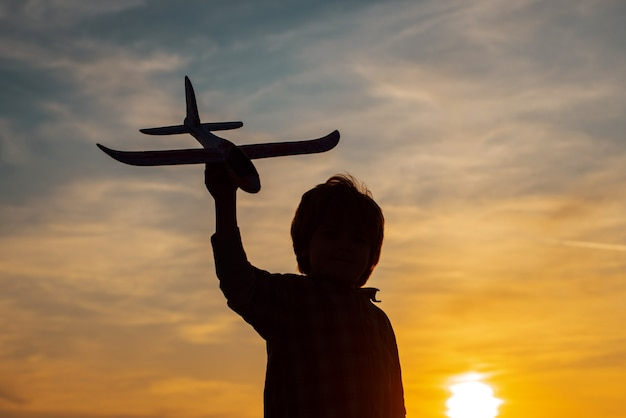 Mały lotnik chłopiec na zachód słońca. małe dzieci z samolocikiem w polu o zachodzie słońca. sukces i