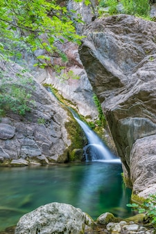 Mały malowniczy wodospad w przytulnej górskiej lagunie.