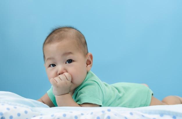 Mały mały azjatykci dziecka niemowlak kłaść na łóżku z jego palcem w usta