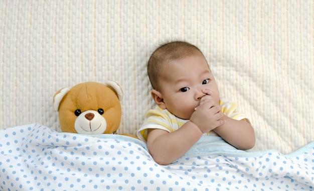 Mały mały azjatykci dziecka niemowlak relaksuje w łóżku z jego palcem w usta