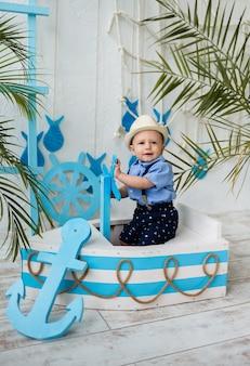 Mały marynarz w garniturze siedzi w niebiesko-białej łodzi i patrzy w kamerę na powierzchnię morskiego wystroju