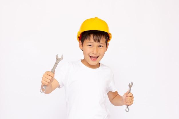 Mały mechanik w kasku trzyma narzędzia