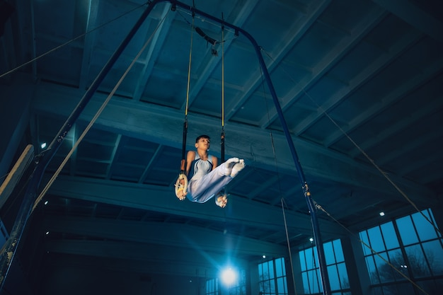 Mały męski gimnastyczka trening na siłowni, elastyczny i aktywny. chłopiec sprawny kaukaski, sportowiec w białej odzieży sportowej ćwiczących w ćwiczeniach dla równowagi na pierścieniach. ruch, akcja, ruch, dynamiczna koncepcja.