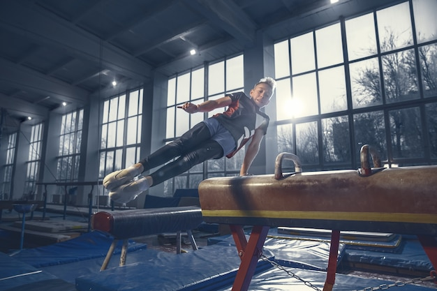 Mały męski gimnastyczka trening na siłowni elastyczny i aktywny
