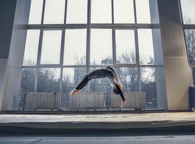 Mały mężczyzna gimnastyczka trening na siłowni, elastyczny i aktywny