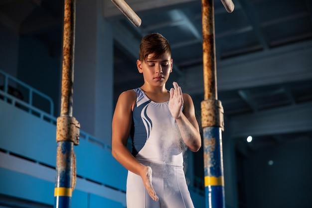 Mały mężczyzna gimnastyczka trening w siłowni elastyczny i aktywny