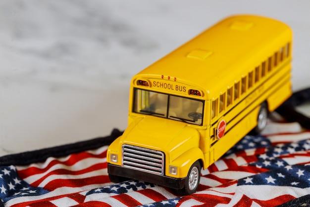 Mały miejski autobus szkolny i flaga amerykańska
