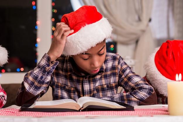Mały mikołaj czyta książkę. chłopiec czytanie książki na boże narodzenie. czytanie bajek świątecznych przy oknie. czas wolny dla dzieci na wakacjach.