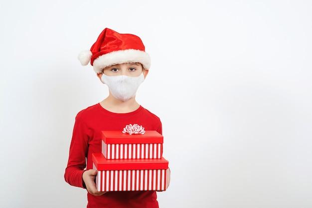 Mały mikołaj z prezentami świątecznymi. dziecko w świątecznej czapce i masce bezpieczeństwa. świąteczne zakupy.