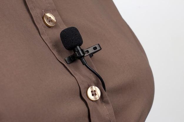 Mały mikrofon audio do nagrywania głosu z spinaczem do bielizny przymocowanym do damskiej koszuli.