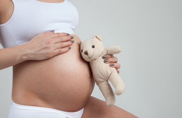 Mały miś nasłuchiwać brzucha kobiety w ciąży na białym tle