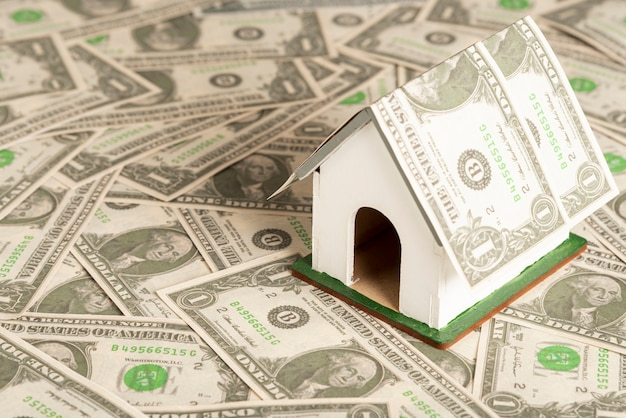 Mały model domu zabawki otoczony pieniędzmi