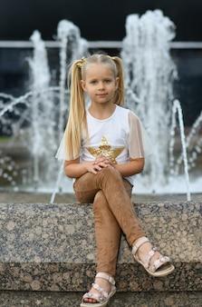 Mały model dziewczyna siedzi w pobliżu fontanny miasta.