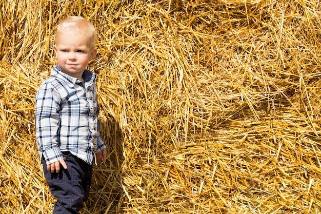 Mały modny chłopiec w tle stogu siana