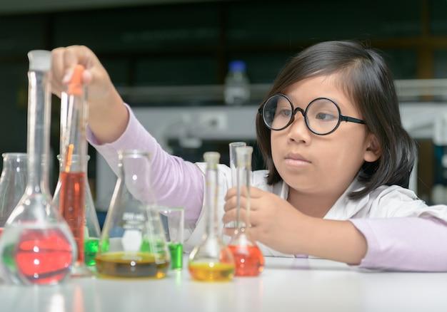 Mały naukowiec w laboratorium płaszcz podejmowania eksperyment