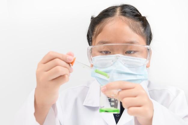 Mały naukowiec za pomocą zakraplacza upuszcza zielony płynny środek chemiczny do zlewki na białym tle. eksperyment naukowy i koncepcja edukacji