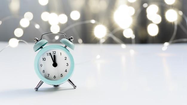 Mały niebieski budzik wskazuje godzinę 12, stoi na podświetlanym stoliku z rozmytym tłem i światłami bokeh. koncepcja bożego narodzenia i nowego roku.