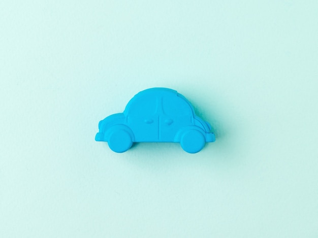 Mały niebieski samochodzik na jasnoniebieskim tle. koncepcja popularnego pojazdu.