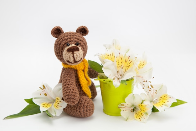 Mały niedźwiedź brunatny z białymi kwiatami, dzianinowa zabawka, ręcznie robiony. amigurumi.