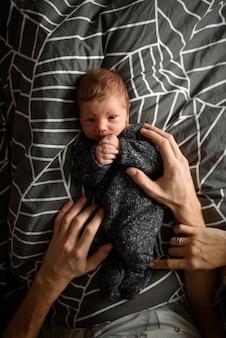 Mały nowonarodzony chłopiec w ósmym miesiącu leży w rękach troskliwych rodziców.