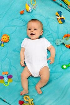 Mały noworodek leży na niebieskim kocu i bawi się zabawkami w świetnym nastroju.