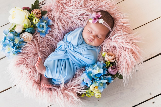Mały noworodek w kwiatowy kosz