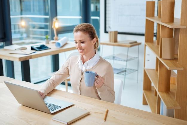 Mały odpoczynek. zajęty wesoła sekretarka popijająca herbatę, patrząc na ekran laptopa i pisząca