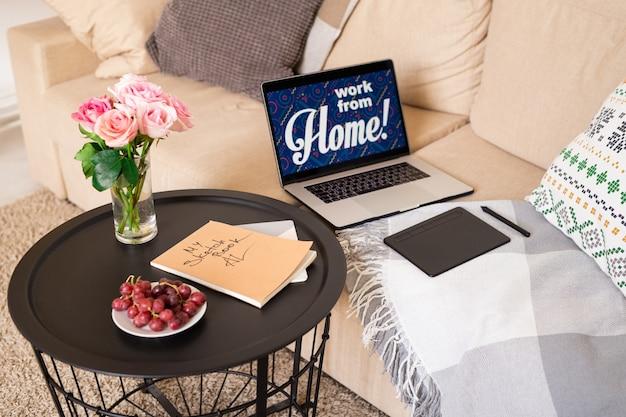 Mały okrągły stół z bukietem róż, świeżych czerwonych winogron na talerzu i książką szkiców stojących przy kanapie z laptopem i podkładką projektanta