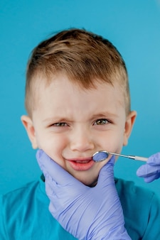 Mały pacjent nie chce otwierać ust dentysty na niebieskim tle. dantist leczy zęby. widok dentysty leczenia zębów małego chłopca w gabinecie dentysty.