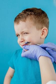 Mały pacjent nie chce otwierać ust dentysty na niebieskim tle