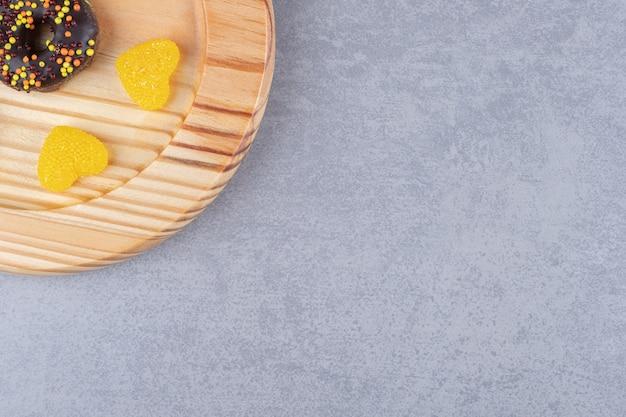 Mały pączek i dwie marmolady na talerzu na marmurowej powierzchni