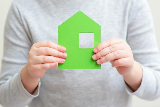 Mały papierowy dom w rękach dziecka