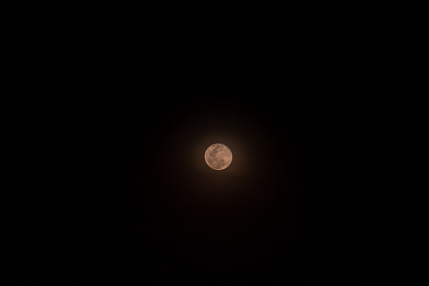 Mały pełny księżyc odizolowywający nad czernią