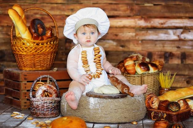 Mały piekarz chłopiec w czapce i fartuchu kucharza wysmarowanym mąką z bułkami na szyi przygotowuje ciasto do pieczenia