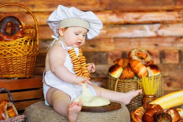 Mały piekarz chłopiec w czapce i fartuchu szefa kuchni z bukietem bajgli na szyi przygotowuje ciasto do pieczenia na tle produktów piekarniczych