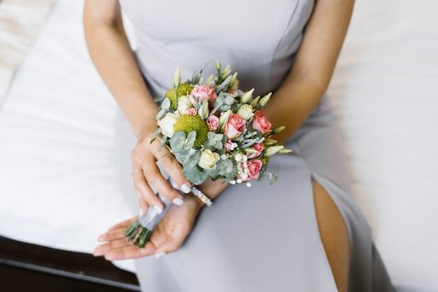 Mały piękny bukiet ślubny w rękach panny młodej z różowych róż, białych eustomi i gałęzi eukaliptusa