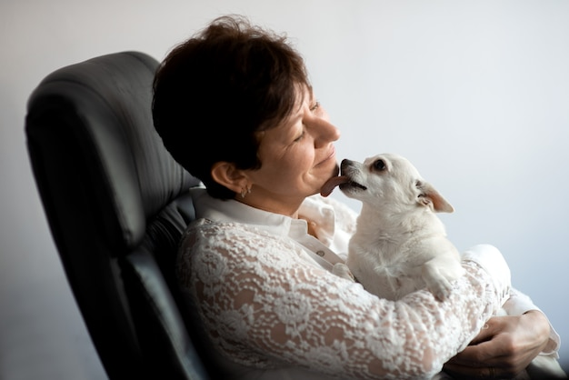 Mały pies liże twarz kobiety w średnim wieku siedzącej na krześle na szarym tle studia
