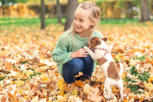 Mały pies rasowy z małą dziewczynką rasy kaukaskiej