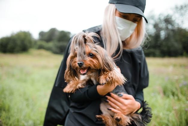 Mały piesek i jej właściciel na spacer po parku. młoda dziewczyna w masce medycznej trzyma yorkshire terrier w ramionach na zewnątrz.