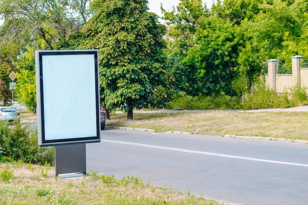 Mały pionowy billboard przy drodze w małym zielonym mieście
