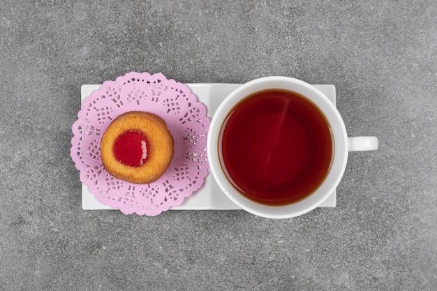 Mały placek z galaretką i filiżanką herbaty na marmurowej powierzchni