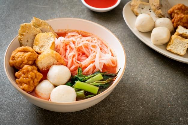 Mały płaski makaron ryżowy z kulkami rybnymi i kulkami krewetkowymi w różowej zupie, yen ta four lub yen ta fo - kuchnia azjatycka