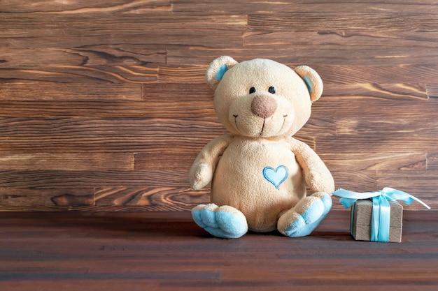Mały pluszowy miś z pudełkiem na drewnianym stole z miejscem na kopię. baby shower, akcesoria, rzeczy, prezent dla chłopca, urodziny pierwszego roku, tło strony noworodka