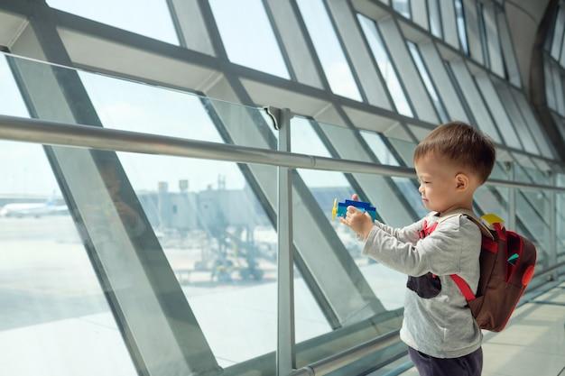 Mały podróżnik, śliczny uśmiechnięty mały azjata 2 lat berbecia chłopiec dziecko ma zabawa bawić się