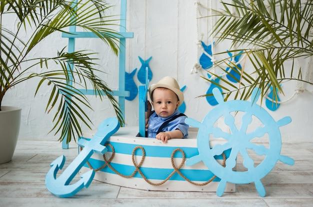 Mały podróżnik w garniturze i słomkowym kapeluszu siedzi w niebiesko-białej drewnianej łodzi na powierzchni z morskim wystrojem