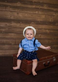 Mały podróżnik w słomkowym kapeluszu siedzi na walizce retro na drewnianej brązowej powierzchni z miejscem na tekst