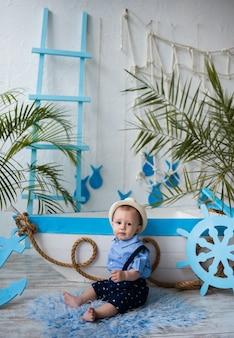 Mały podróżnik w słomkowym kapeluszu siedzi w pobliżu niebiesko-białej łodzi na białej powierzchni z morskimi dekoracjami